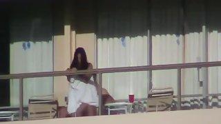 Couple filmed poking on hotel balcony