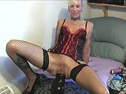 Mature blondie squeezing huge fucktoys inside her